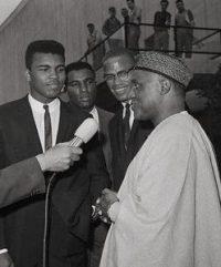 Muhammad Ali e Elijah Muhammad (fundador do grupo político-religioso Nação do Islã), com Malcolm X ao fundo